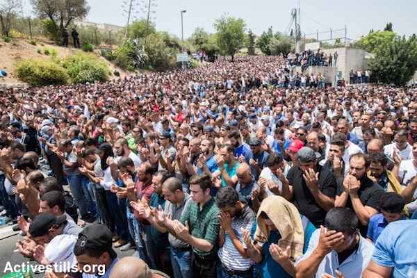 Palestinian worshipers hold a mass prayer in the streets of East Jerusalem as an act of civil disobedience after Israel implemented new entry arrangements for Al-Aqsa Mosque, Wadi Joz, East Jerusalem, July 21, 2017. (Yotam Ronen/Activestills.org)