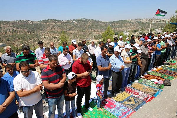 Dozens of Palestinians hold a mass prayer to protest the planned demolition of 14 buildings in their village of Walajeh, West Bank, August 18, 2017. (Ahmad Al-Bazz/Activestills.org)