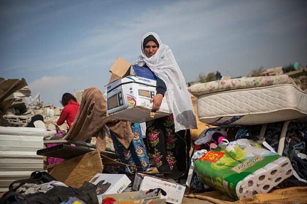 Bedouin women collect their belongings from the ruins of their demolished homes in the village of Umm al-Hiran, Negev desert, January 18, 2017. (Hadas Parush/Flash90)