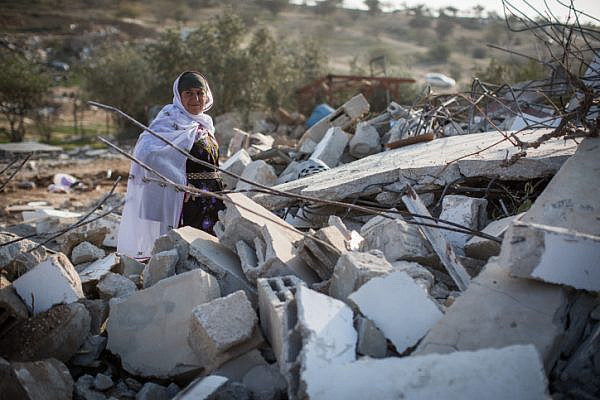Bedouins collect their belongings from the ruins of their demolished homes in the Bedouin village of Umm al-Hiran, January 18, 2017. (Hadas Parush/Flash90)