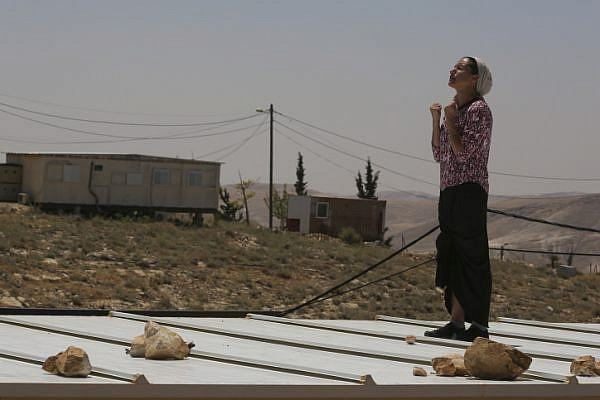A settler stands and prays on top of her home roof during the demolition and evacuation of 10 structures in the Ma'ale Rehavam outpost, West Bank, May 14, 2014. (Nati Shohat/Flash 90)