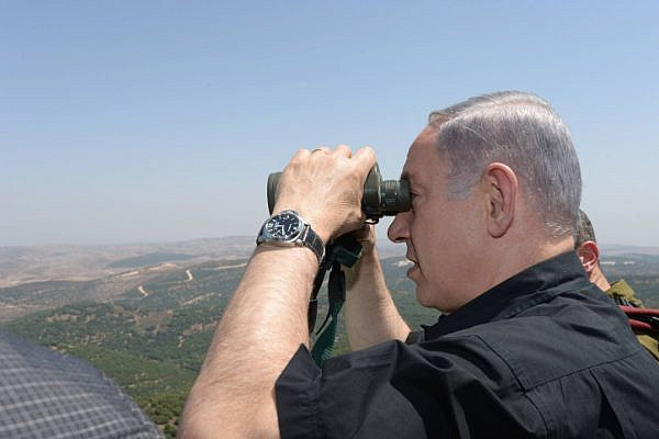Israeli Prime Minister Benjamin Netanyahu looks through binoculars during his visit to the border with Syria, August 18, 2015. (Amos Ben Gershom/GPO)
