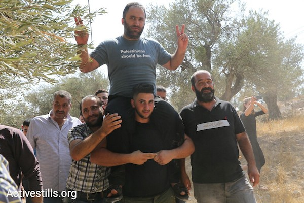 aPalestinian anti-occupation activists Issa Amro is carried on the shoulders of a fellow activist upon his release from Palestinian Authority custody in Hebron, September 10, 2017. (Oren Ziv/Activestills.org)