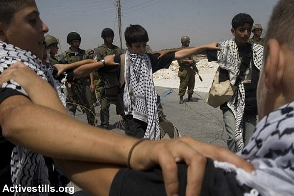 Palestinian youth perform a Dabke dance routine in front of soldiers during a protest against the separation wall, Al Ma'sara, West Bank, August 22, 2008. (Oren Ziv/Activestills.org)