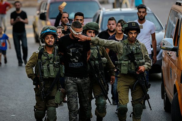 Israeli soldiers arrest a Palestinian man during a raid on the West Bank city of Hebron, September 20, 2017. (Wisam Hashlamoun/Flash90)