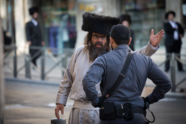An ultra-Orthodox Jewish man argues with an Israeli police officer during a demonstration against businesses that operate on Saturdays in Jerusalem, August 12, 2017. (Yonatan Sindel/Flash90)