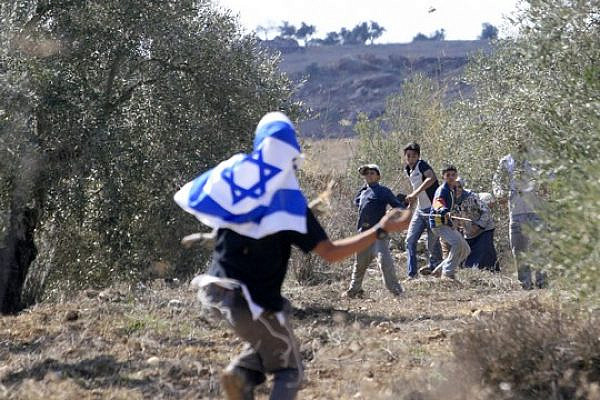 An Israeli settler, masked with an Israeli flag, and Palestinian boys throw stones during clashes at an olive harvest close near Nablus, Wednesday 25, 2006. (Olivier Fitoussi/Flash90)