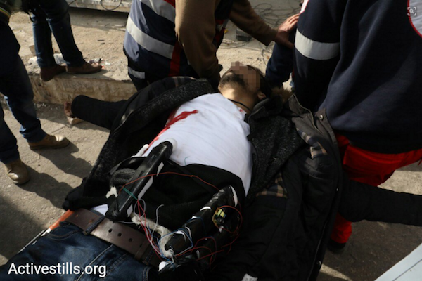 A Palestinian man with an explosive belt is seen carried by paramedics after being shot by Israeli soldiers during clashes at the DCO Checkpoint, Beit El, West Bank. The man attempted to stab Israeli soldiers shooting tear gas at the demonstrators. Upon falling to the ground, he revealed an explosive belt strapped to his body. (Oren Ziv/Activestills.org)