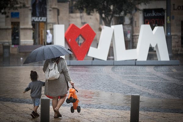 People hold umbrellas to protect themselves from the rain as they walk on Jaffa Street in downtown Jerusalem, October 9, 2017, (Yonatan Sindel/Flash90)