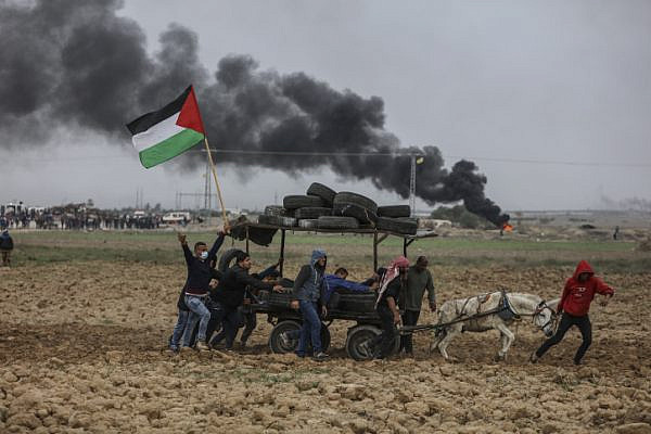 Palestinian protesters chant as they surround a donkey cart loaded with tires during clashes with Israeli troops on the Israeli border with Gaza. December 22, 2017. (Wissam Nassar/Flash90)