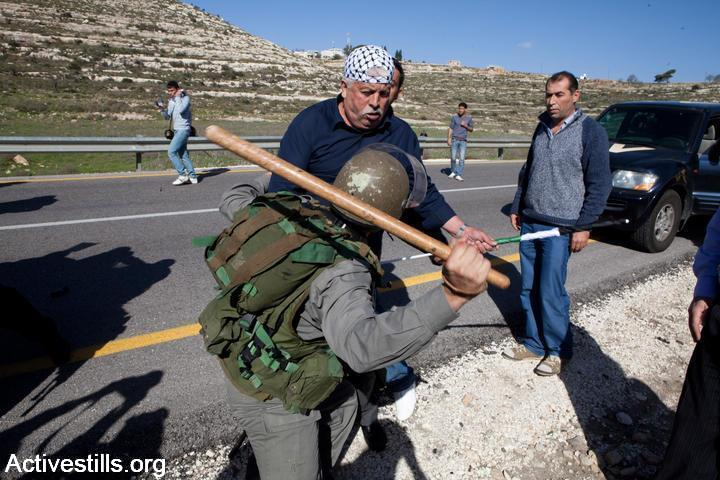 An Israeli Border Police officer beats a Palestinian protester with a club during a demonstration in Nabi Saleh, January 15, 2010. (Yotam Ronen/Activestills.org)