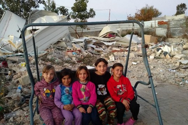 Issam Rajbi's children sit in front of the ruins of their home, Beit Hanina, East Jerusalem.