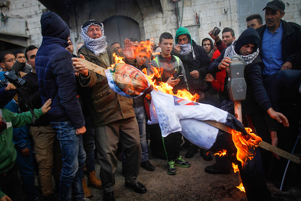 Palestinian burns the doll a poster depicting U.S. President Donald Trump during a protest against US President Donald Trump's announcement that he recognized Jerusalem as the capital of Israel, in the West Bank city of Nablus, on December 7, 2017. (Nasser Ishtayeh/Flash90)