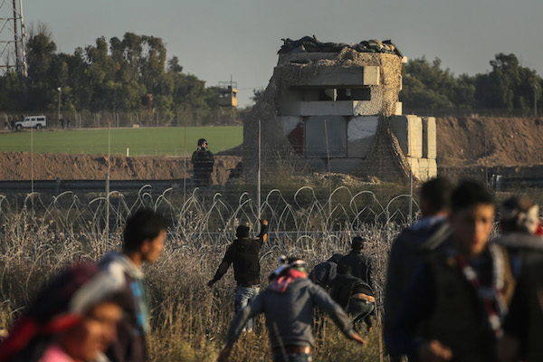 Palestinian protesters inside the Gaza Strip throw stones in the direction of an Israeli military position on the other side of the border fence, Gaza Strip, December 8, 2017. (Ezz Zanoun/Activestills.org)