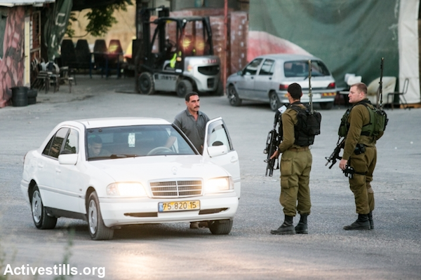 Israeli soldiers stop Palestinians at a flying checkpoint at the entrance to the West Bank city of Hebron, June 15, 2014. (Yotam Ronen/Activestills.org)
