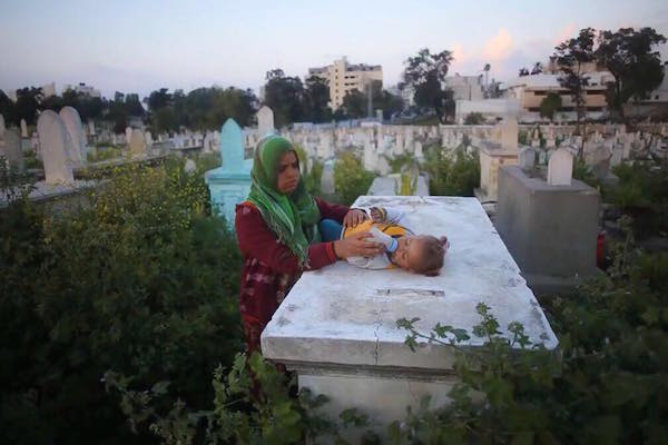 A woman with her baby in a Gaza cemetery. (Photo by Mohammed Abu Nahel)