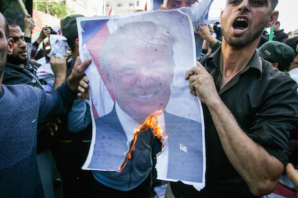 Palestinian burning a picture of US President Donald Trump during a protest against US President Donald Trump's latest decision to recognized Jerusalem as the capital of Israel, in Rafah, in the Southern Gaza Strip on December 8, 2017. (Abed Rahim Khatib/Flash90)