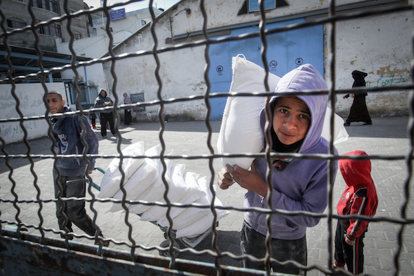 Palestinian refugees collect aid parcels at a United Nations food distribution centre in Rafah, in the southern Gaza Strip on January 21, 2018. (Abed Rahim Khatib/ Flash90)