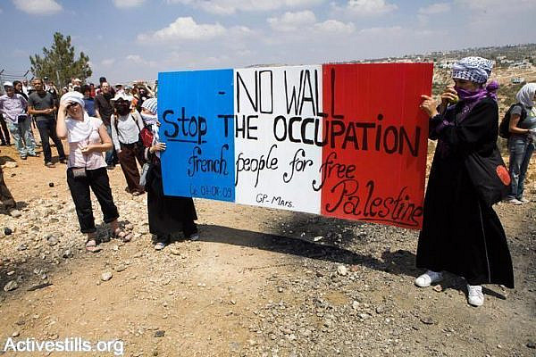 Women activisits hold up signs during an action that attempts to dismantle a barbed wire part of the gate of the Seperation Wall in Bil'in, as part of the weekly protest against the Separation Wall and the occupation, West Bank, August 14, 2009. Hundreds of Palestinians, Israeli, and international activists, responded to the Popular Committee's call to resist to participate in the action. (Yotam Ronen/Activestills.org)