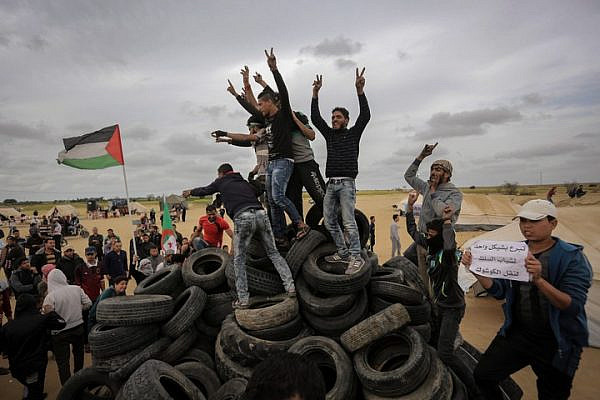 Palestinians youth collect tires to burn them during demonstrations in Khan Yunis, southern Gaza Strip, April 4, 2018. (Abed Rahim Khatib/Flash90)