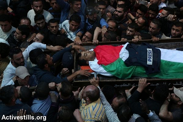 Mourners and fellow journalists carry the body of Yasser Murtaja at his funeral in Gaza City, April 7, 2018. Murtaja was shot and killed by Israeli soldiers during the Great Return March in the southern Gaza Strip. (Mohammed Zaanoun/Activestills.org)