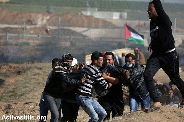Palestinian protesters evacuate a fellow demonstrator who was shot by an Israeli sniper during the Great Return March protest, east of Jabaliya, Gaza Strip, April 6, 2018. (Mohammed Zaanoun/Activestills.org)