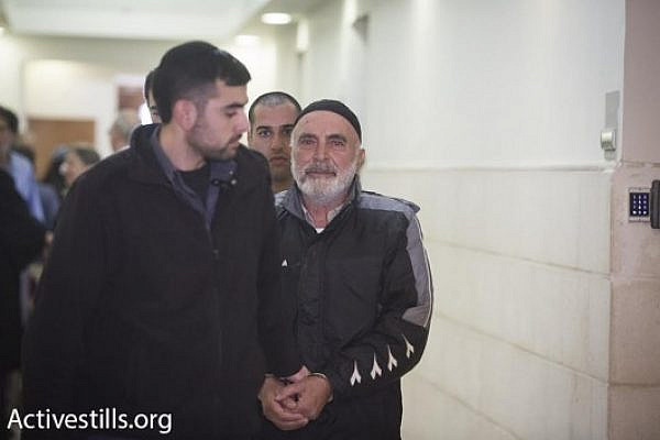 eft-wing activist Ezra Nawi is led into the Jerusalem Magistrate's Court, January 21, 2016. (Oren Ziv/Activestills.org)