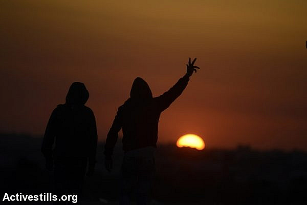 Palestinians seen at sunset during a protest as part of the Great Return March, near the Israeli-Gaza fence, eastern of Jabaliya refugee camp, Gaza Strip, April 23, 2018. (Mohammed Zaanoun/Activestills.org)