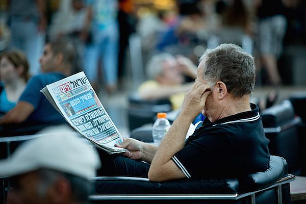 "Illustrative photo of a man reading ""Israel Hayom,"" the Sheldon Adelson-funded newspaper (Moshe Shai/FLASH90)."