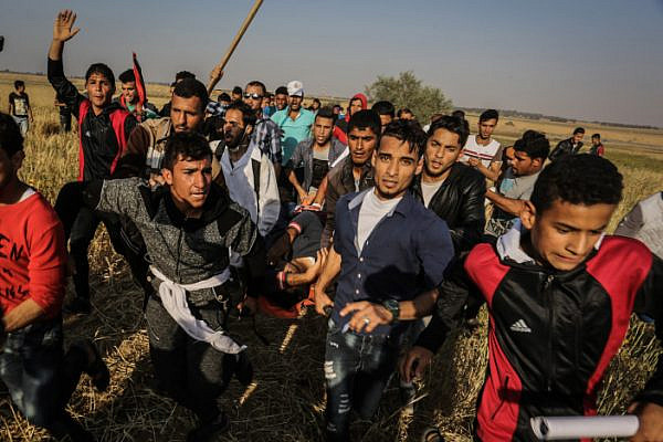 Palestinians carrying a wounded Palestinian man at the Israel-Gaza border, during the Great Return March, Khan Younis in the southern Gaza Strip, April 15, 2018. (Abed Rahim Khatib/Flash90)