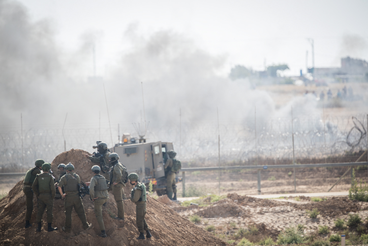 Israeli soldiers shoot tear gas is shot at Palestinian protesters on the border with the Gaza Strip, as Palestinians demonstrate to mark Naksa Day, June 8, 2018. (Yonatan Sindel/Flash90)