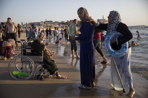 Palestinians from the West Bank enjoy the beach in Tel Aviv- Jaffa during the Eid al-Fitr holiday. June 17, 2018. (Oren Ziv/Activestills.org)