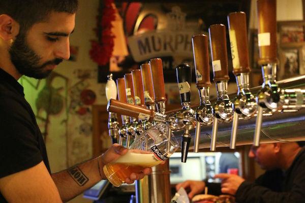 A bartender pours a pint at Kamun Pub. (Steven Davidson)