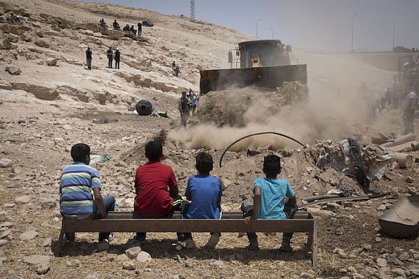 Residents of the Bedouin village Khan al-Ahmar look on as a bulldozer paves an access road to be used by Israeli forces in the imminent demolition of the West Bank hamlet, July 4, 2018. (Oren Ziv)