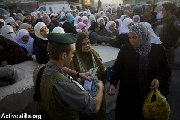 An Israeli soldier checks women's IDs, Qalandiya checkpoint, West Bank, August 20, 2010. (Oren Ziv/Activestills.org)