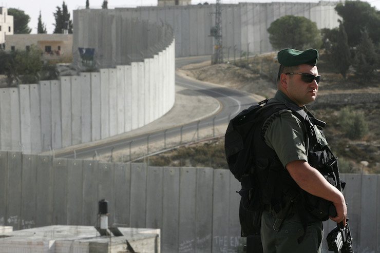 An Israeli Border Police officer is seen in front of Israel's separation barrier in Abu Dis, West Bank. (Kobi Gideon/Flash90)