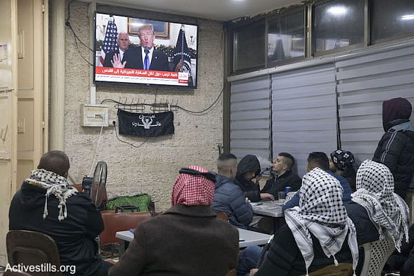 Palestinian men watch Donald Trump give a foreign policy speech in a cafe in East Jerusalem, December 6, 2017. (Oren Ziv/Activestills.org)