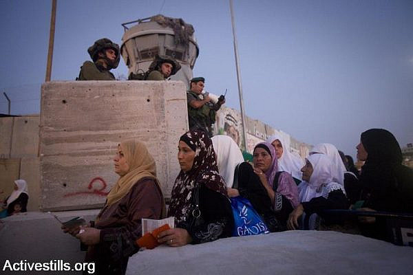 Israeli soldiers watch Palestinian women walk towards Qalandiya checkpoint, West Bank, August 20, 2010. (Oren Ziv/Activestills.org)