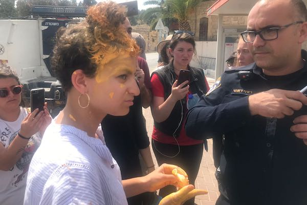 Breaking the Silence staffer Frima (Murphie) Bubis is seen speaking with Israeli police after a settler child threw paint on her head during a tour in Hebron, July 16, 2018. (Mairav Zonszein)