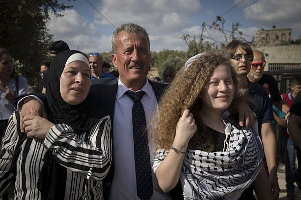 Nariman Tamimi (left), Bassem Tamimi (center), and Ahed Tamimi (right) walk into Nabi Saleh after Nariman and Ahed are released from Israeli prison, July 29, 2018. (Oren Ziv)