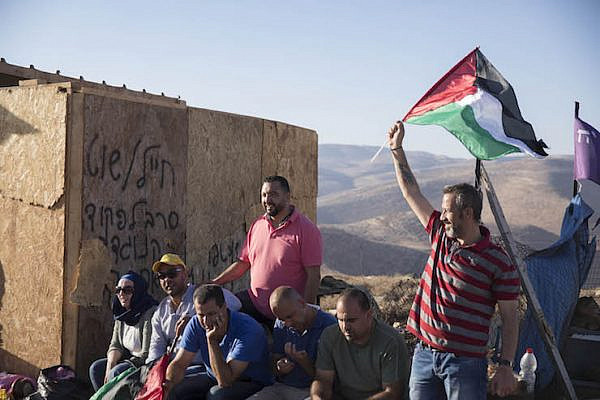 The villagers of Ein Samia wave Palestinian flags at an abandoned structure built by settlers, as part of the notoriously radical Baladim outposts, August 15, 2018. (Oren Ziv/Activestills.org)