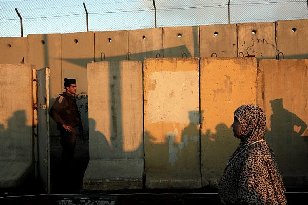 A Muslim Palestinian worshipper headed to the Al-Aqsa compound in Jerusalem walks by an Israeli soldier as she crosses the Qalandia checkpoint on August 05, 2011 (Miriam Alster/ Flash90).