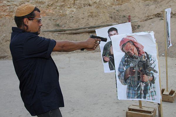 Jewish settlers train firing at pictures of terrorists at the Gush Etzion shooting range on July 18, 2012. (Gershon Elinson/Flash90)