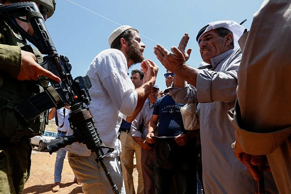 An Israeli settler argues with Palestinians during a protest against a new tent placed by Jewish settlers near the West bank village of Bani Naem on June 23, 2018 (Wisam Hashlamoun/Flash90).