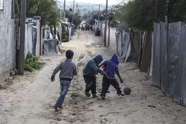 Palestinian refugees play in an impoverished area in Gaza City on January 17, 2018, after the White House froze tens of millions of dollars in aid to UNRWA. (Wissam Nassar/Flash90)