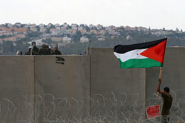 A Palestinian protester holds the Palestinian flag near the Israeli separation wall as Israeli security officers look on during a protest in the West Bank village of Bil'in near Ramallah on September 9, 2011. (Issam Rimawi/Flash90)