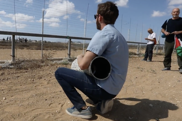 An Israeli activist plays the darbuka for Palestinian protesters on the other side of the Gaza-Israel fence. (Screenshot by Haim Schwarczenberg)