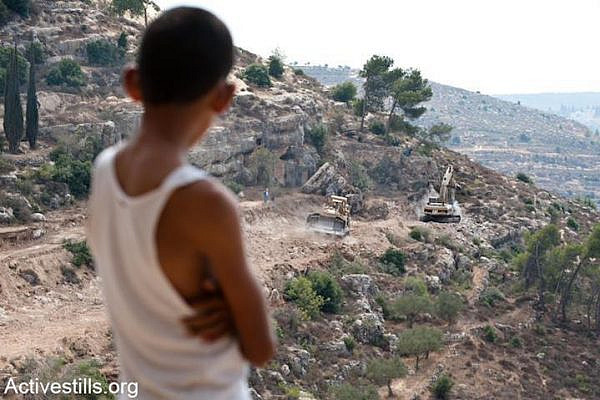 A Palestinian boy watches a bulldozer clearing land for the Israeli separation wall surrounding the West Bank village of al-Walaja, September 5, 2011. (Ryan Rodrick Beiler)