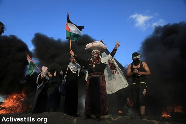 Palestinian protesters waive the Palestinian flag, during a Great Return March demonstration near the Gaza-Israel fence, Gaza Strip, September 7, 2018. (Mohammed Zaanoun/Activestills.org)