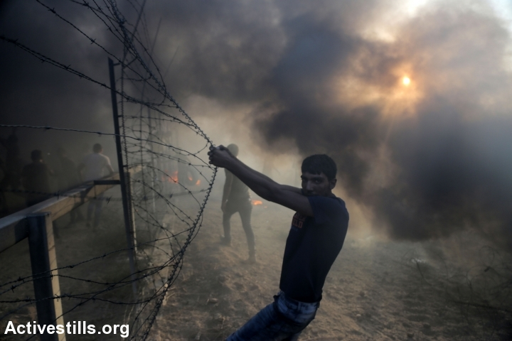 Palestinian protesters seen at the Gaza border fence, during a 'Great Return March' protest, Gaza Strip, September 28, 2018. (Mohammed Zaanoun/Activestills.org)